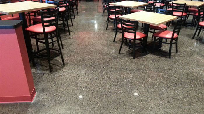 speckled concrete floor with restaurant tables.