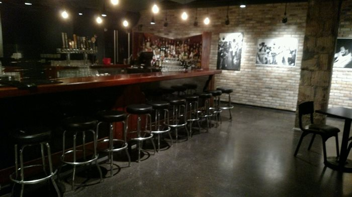 concrete floor with dark wood bar, stools, and brick walls.