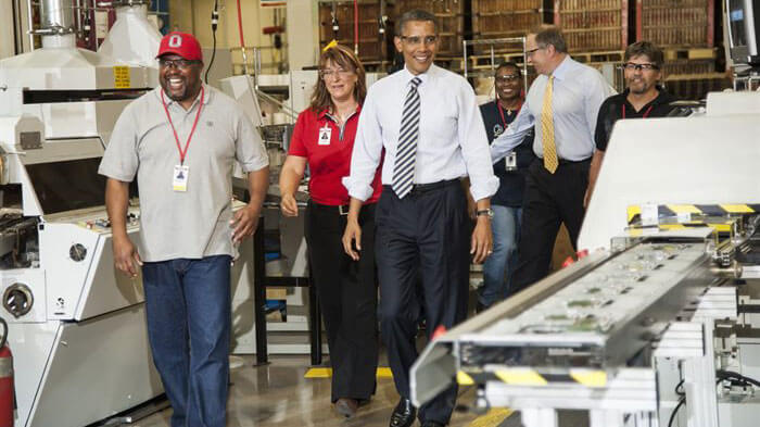 President Obama walking on concrete floor with Honeywell employees.